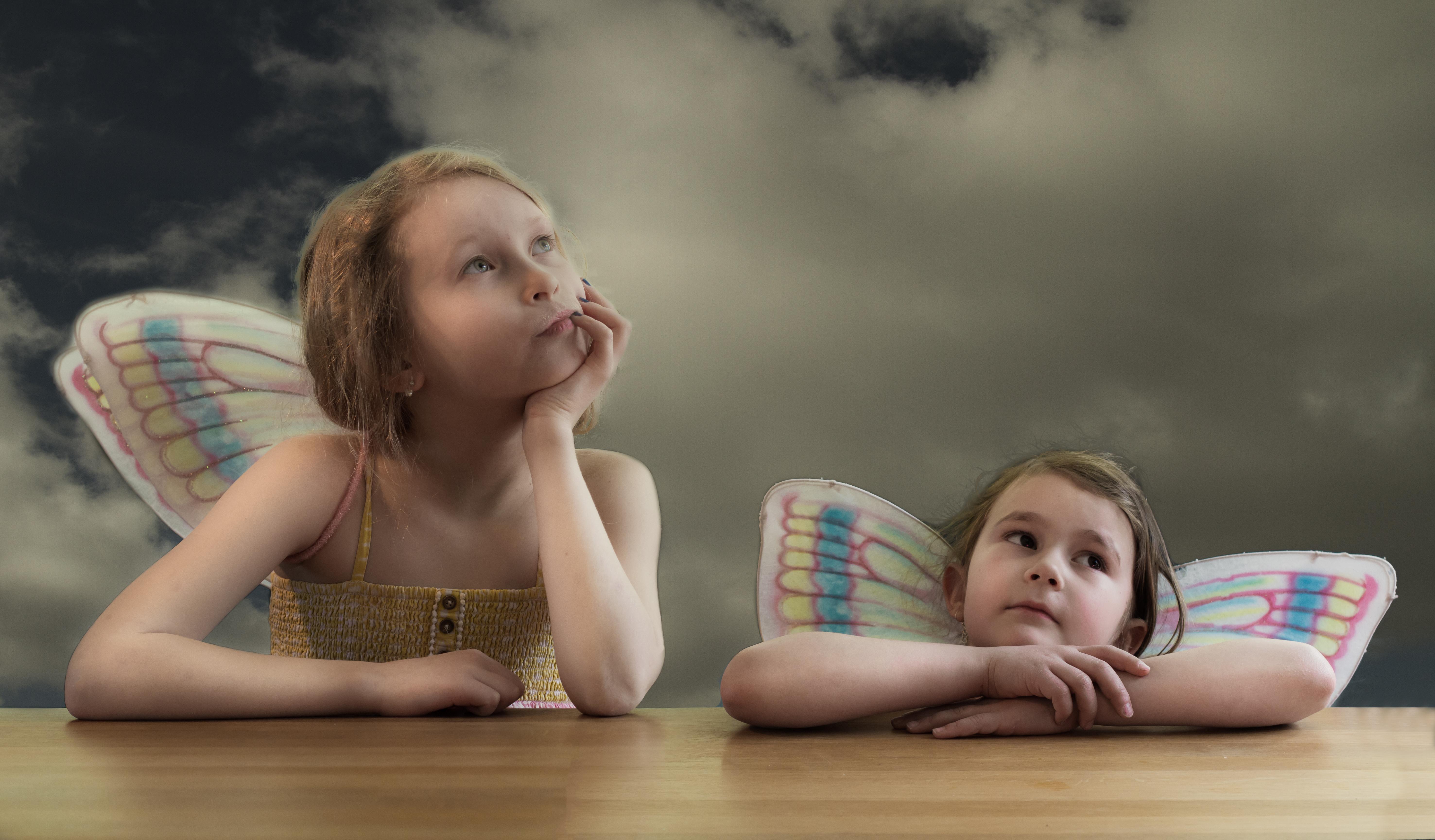 Två flickor iklädda fjärilsvingar, sittandes i samma pose som i Michelangelos ängeltavla.