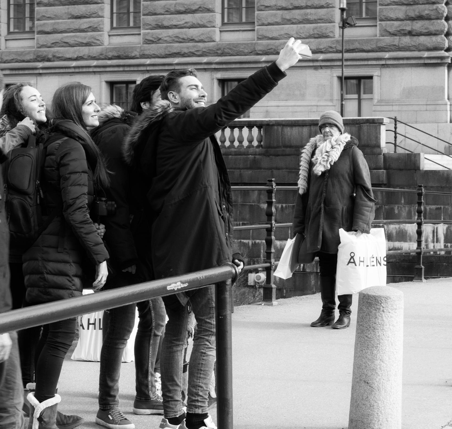 En grupp ungdomar tar en mobilselfie och en dam väntar tålmodigt på att kunna passera.