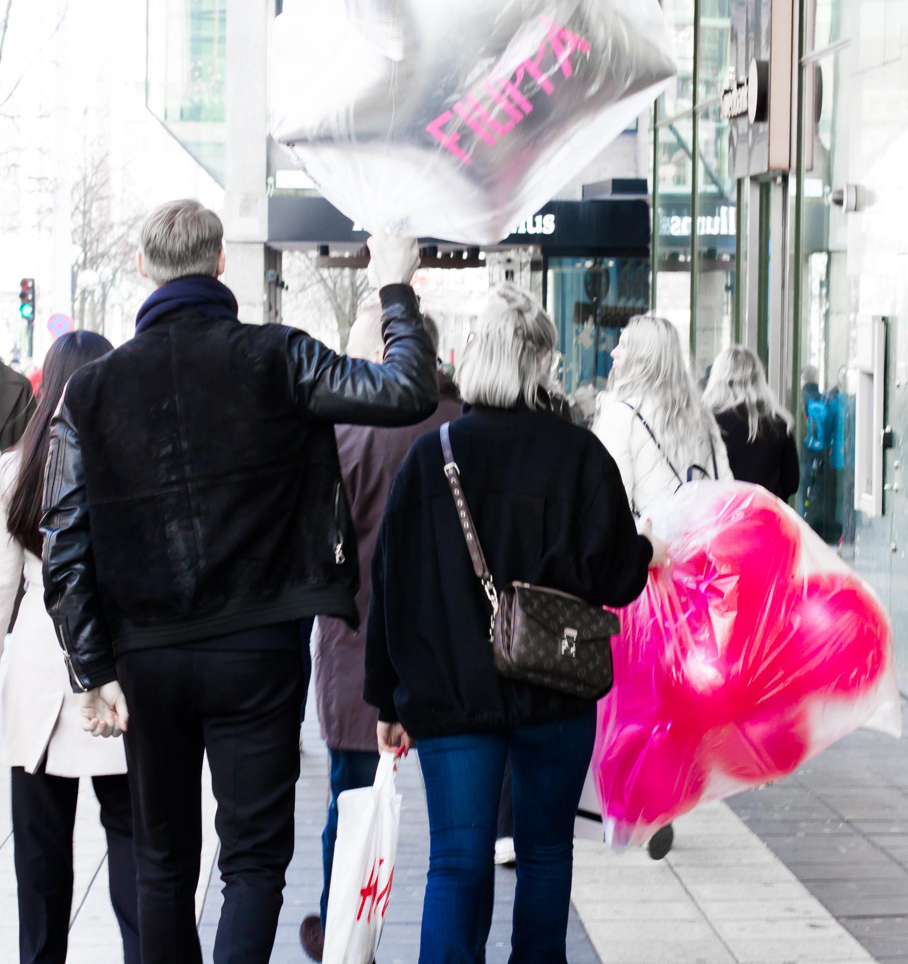 Två personer bär varsin stor plastpåse med ballonger.