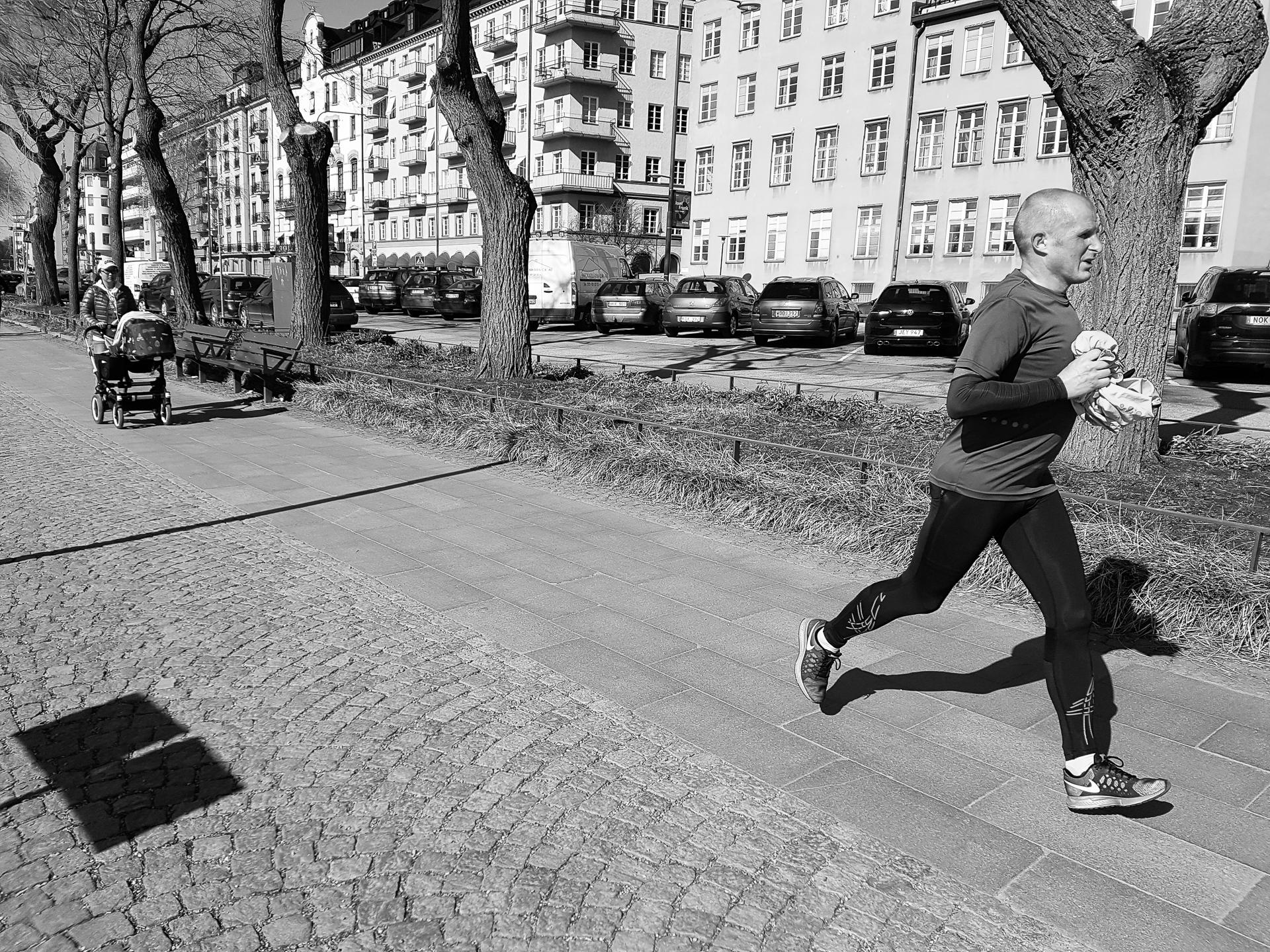 En löpare och en person med barnvagn som springer och promenerar vid almarna.