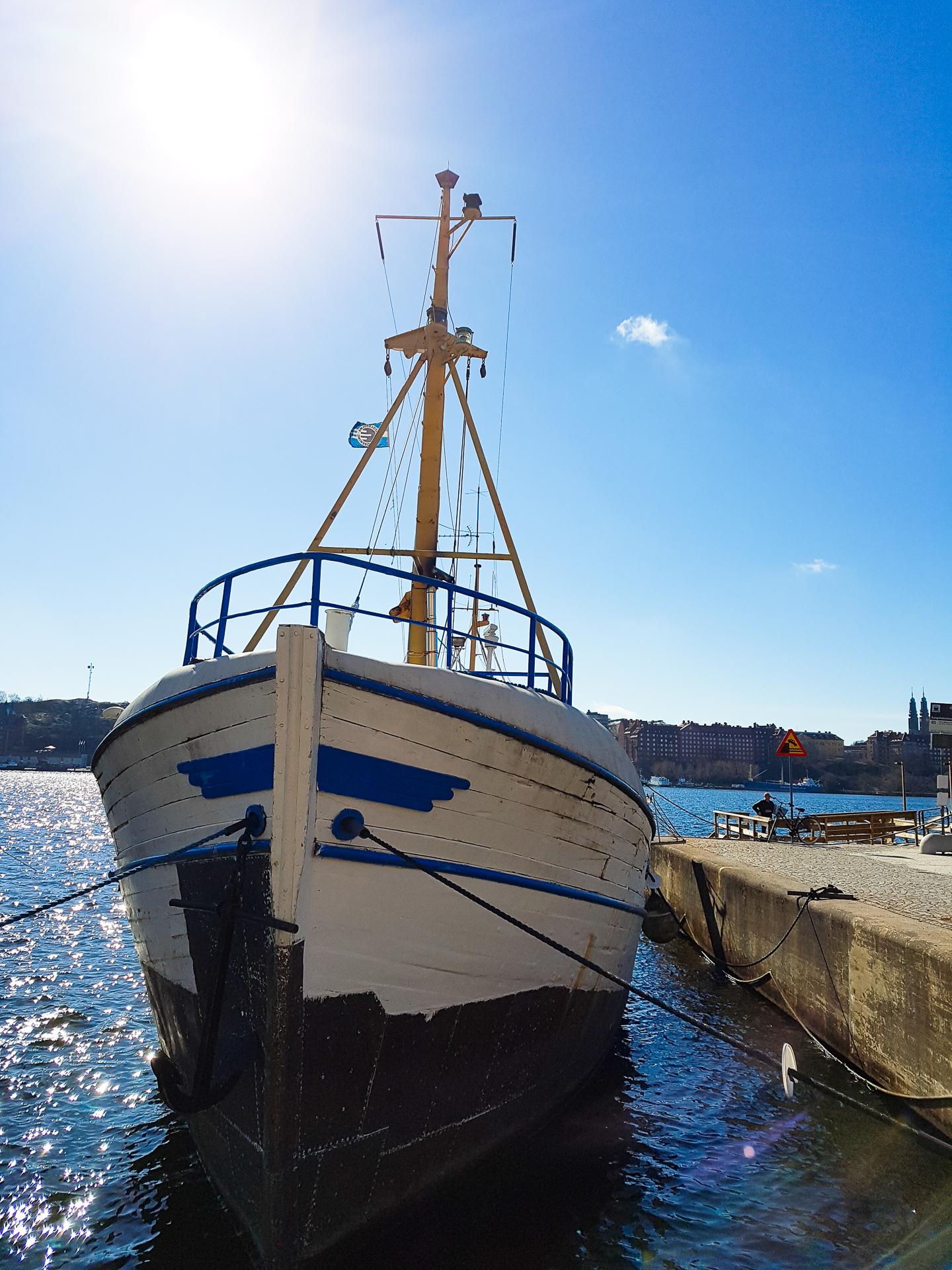 Bild på en båt vid kajen, i motljus