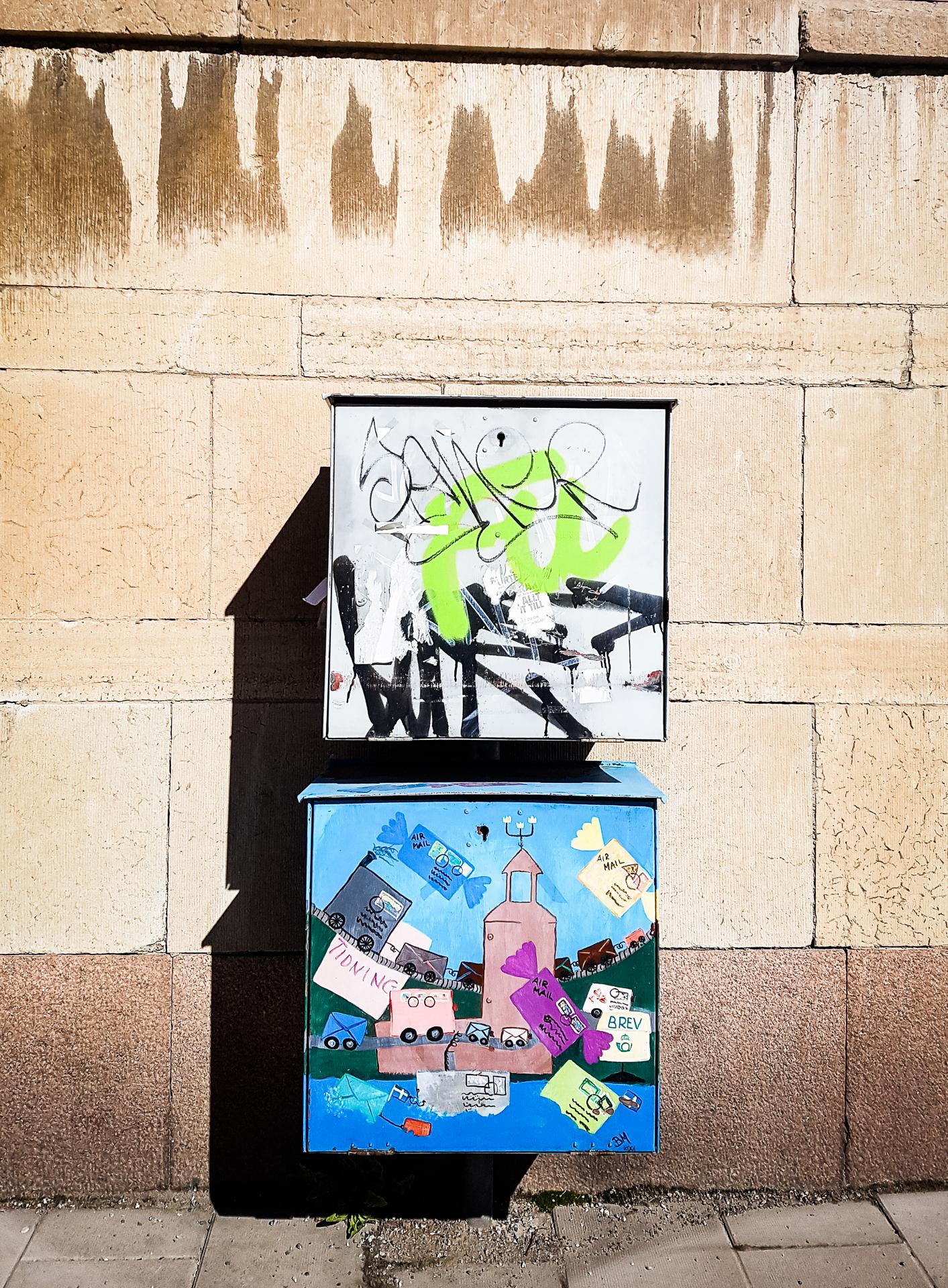 Två graffitimålade postskåp
